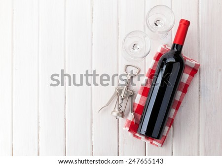 Red wine bottle, glasses and corkscrew on white wooden table background with copy space - stock photo