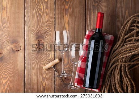 Red wine bottle, glasses and corkscrew over rustic wooden table background with copy space  - stock photo
