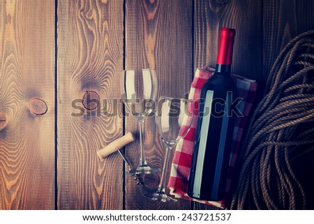 Red wine bottle, glasses and corkscrew over rustic wooden table background with copy space. Retro toned - stock photo