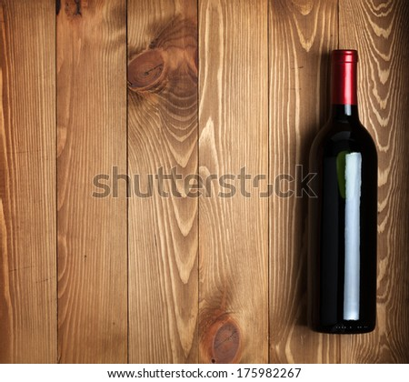 Red wine bottle on wooden table background with copy space - stock photo