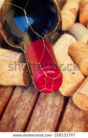 red wine bottle with corks on wooden table, retro toned - stock photo