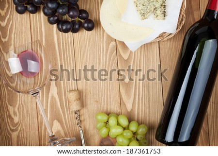 Red wine, cheese and grape on wooden table background with copy space - stock photo