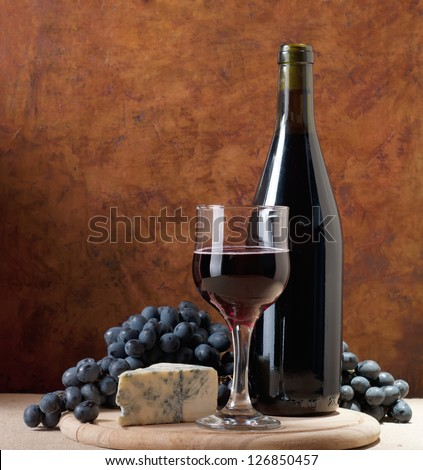 Red wine, cheeses and grapes in a still life setup. - stock photo