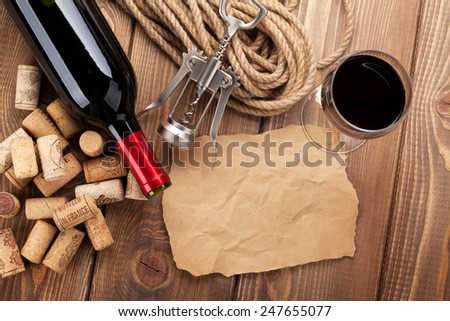 Red wine, corks, corkscrew and piece of paper for copy space on wooden table background - stock photo