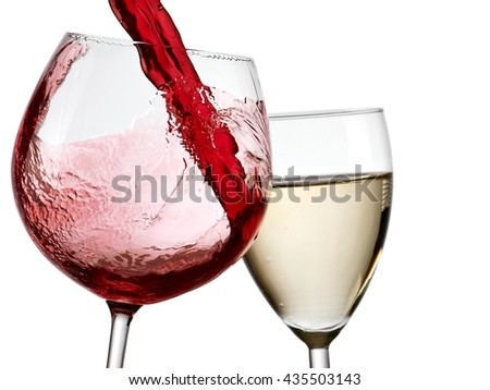 Red wine flow in a glass and a glass of white wine - stock photo