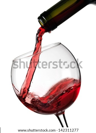 Red wine flow in a glass from a bottle - stock photo