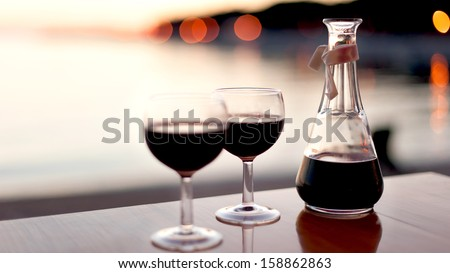 red wine for two in sunset - stock photo