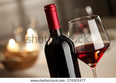 Red wine glass and bottle close up with restaurant on background. - stock photo
