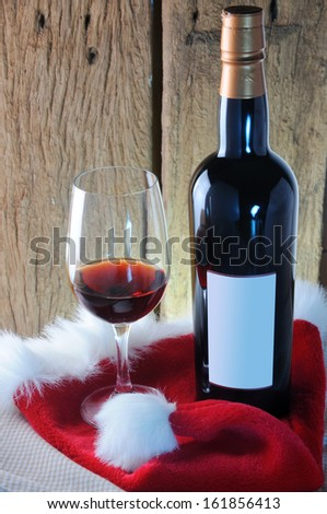 Red wine glass and bottle with red santa hat on wooden background; Christmas concept - stock photo