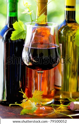 Red wine  glass and grapevine leaves and bottles. - stock photo