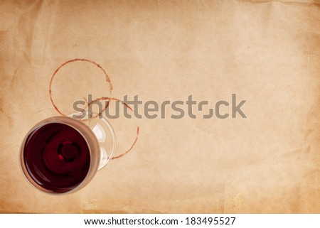 Red wine glass and stains on brown paper background with copy space - stock photo