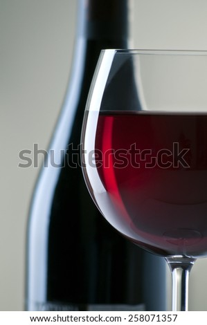 red wine glass close up, bottle background - stock photo