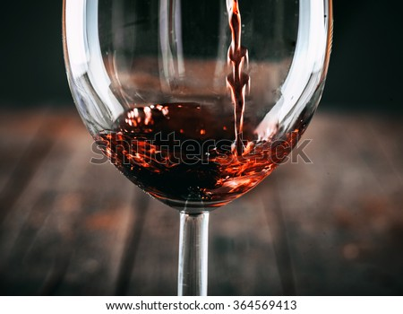 Red wine. Glass of wine. Pouring red wine. - stock photo