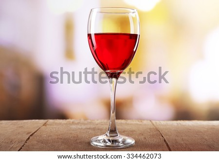 Red wine glass on wooden table against unfocused background - stock photo