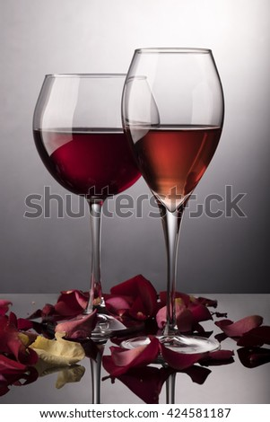 Red wine glass, rose wine glass and rose-petals on black - stock photo