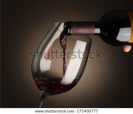 red wine glass with bottle isolated on dark background - stock photo