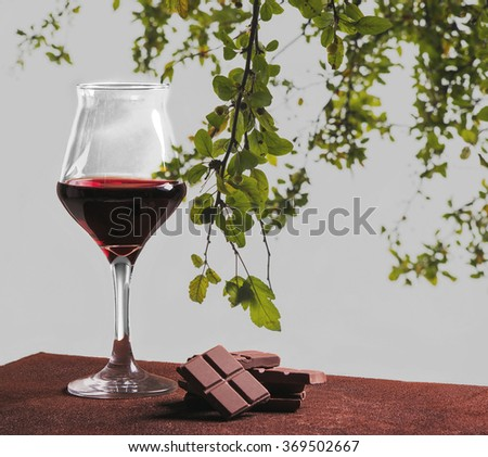 Red wine glass with chocolate and green leaves - stock photo
