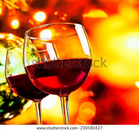 red wine glasses against colorful unfocused lights background, festive and fun concept - stock photo