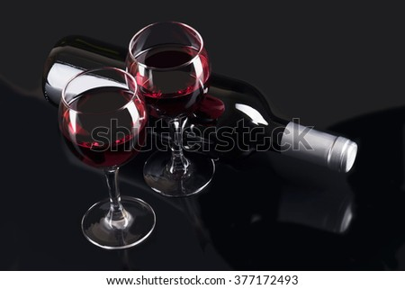 Red wine glasses and red wine bottle isolated on black - stock photo