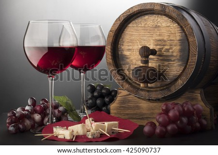 Red wine glasses, cheese, grape vine and old wooden barrel - stock photo