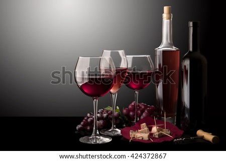 Red wine glasses, rose wine glass, bottle of red wine, bottle of rose wine, cheese and vine  - stock photo