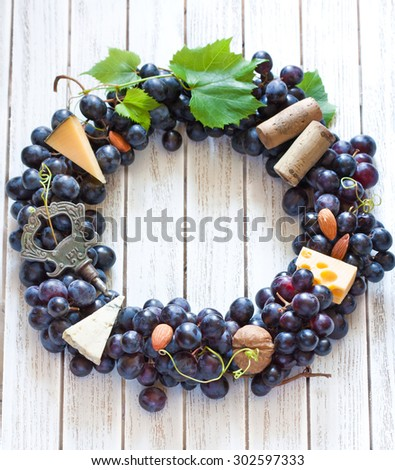 Red wine grape wreath decorated cheese, nuts and old corkscrew hanging on wooden board with place for text or invitation. Vintage style.  - stock photo