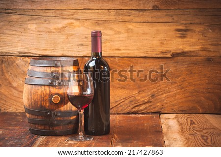 Red wine in a glass with a bottle and barrel on wooden rustic table - stock photo