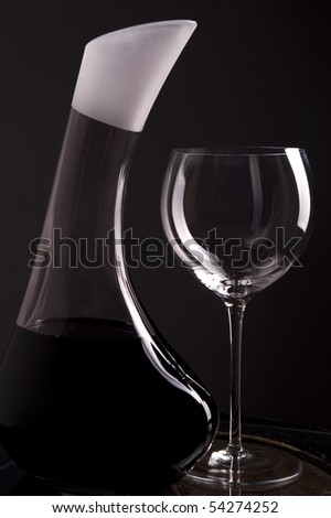 Red wine in decanter with an empty glass beside isolated on dark background - stock photo