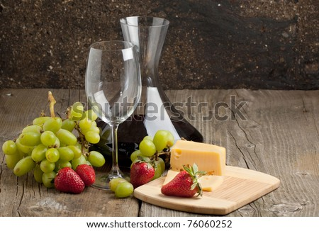 Red wine in decanter with grapes, strawberries and cheese on old wooden table - stock photo