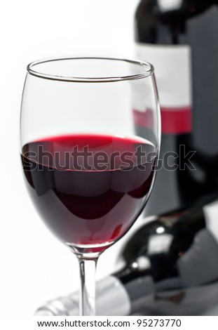 Red wine in glass and bottles, isolated, white background - stock photo