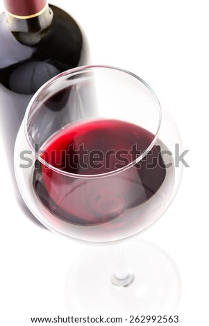 Red wine in glass with bottle isolated on white background. Top view selective focus image - stock photo