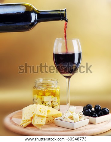 Red wine in wineglass, cheese and olives - stock photo
