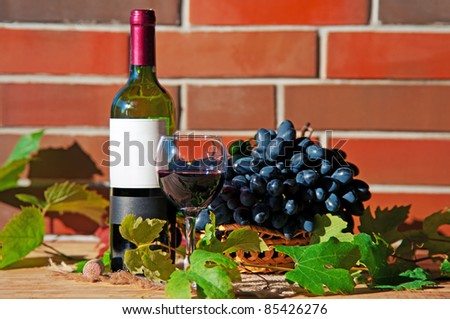 Red wine in wineglass with grape and leaves near brick wall - stock photo