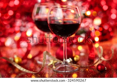 Red wine in wineglasses  against holiday lights background. - stock photo