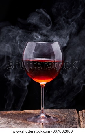 Red wine into the glass in wooden table and smoke - stock photo