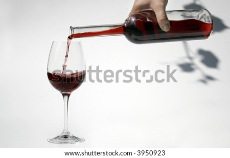 red wine is poured into a glass. Shadow of a vine in the background - stock photo