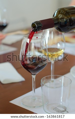 Red wine is pouring into wine glass - stock photo