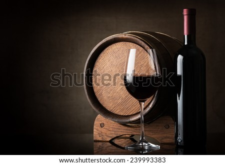 Red wine near wooden barrel on a brown background - stock photo