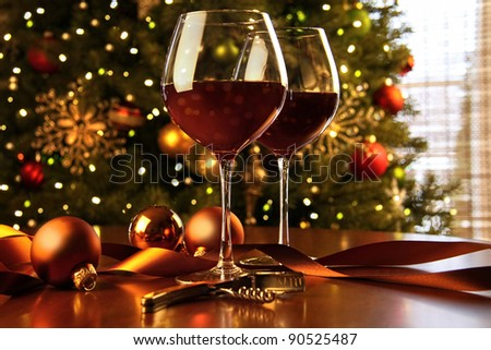 Red wine on table Christmas tree in background - stock photo