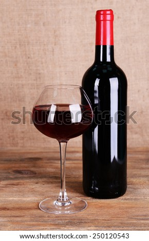 Red wine on table on sack background - stock photo