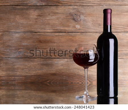 Red wine on table on wooden background - stock photo