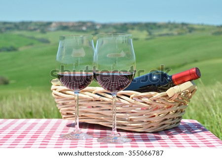 Red wine on the checkered cloth against Tuscan landscape. Italy - stock photo