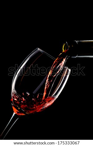 Red wine poured into a glass on black background - stock photo