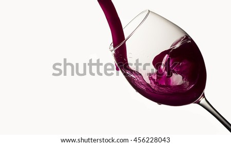 Red wine pouring in a wineglass on white - stock photo