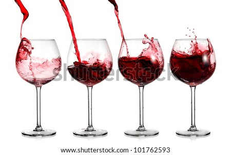 Red wine pouring in four glasses - stock photo