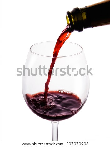 Red wine pouring in to the beautiful wine glass. Isolated on white with Clipping path.  - stock photo