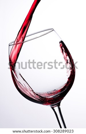 Red wine pouring into a wine glass isolated on white background - stock photo