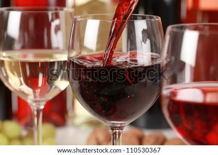 Red wine pouring into a wine glass. Selective focus on the red wine. - stock photo