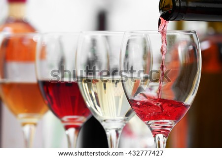Red wine pouring into glasses, closeup - stock photo