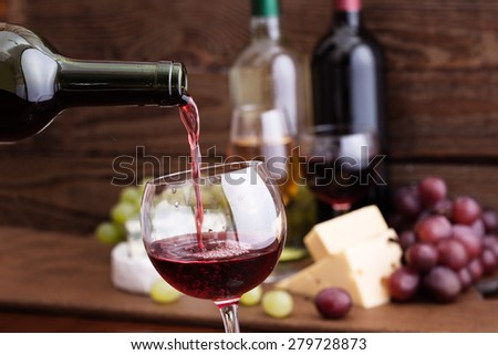 Red wine pouring into wine glass, close-up. ?heese, grapes and wine bottles on wooden table in restaurant. Flat mock up for design  - stock photo